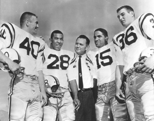 Minnesota coach Murray Warmath meets with the offensive backfield for the national champion Gophers, who lost to Washington in the 1961 Rose Bowl: halfback Dave Mulholland (40), halfback Bill Munsey (28), quarterback Sandy Stephens (15) and fullback Roger Hagberg (36). (Associated Press file photo)